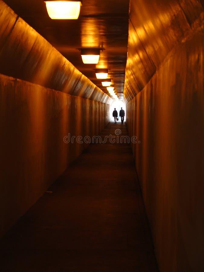 Zwei Leute, die durch Bürgersteig-Tunnel gehen   stockfotos