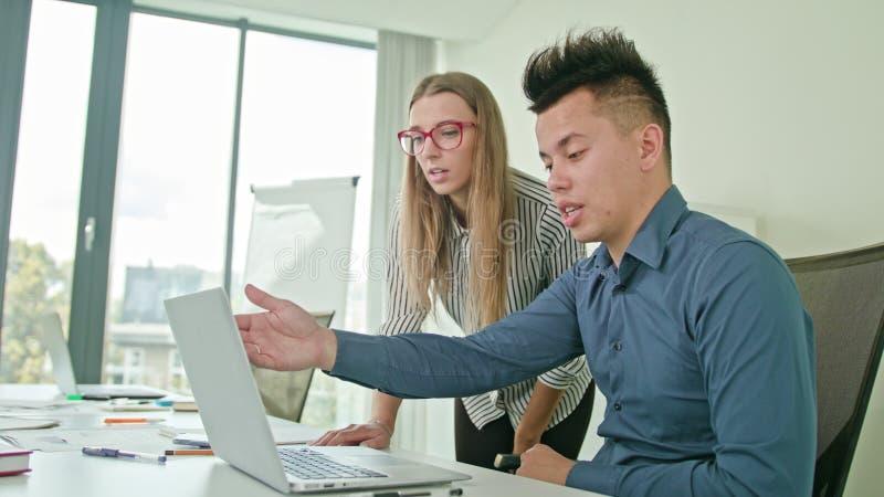 Zwei Leute, die Ideen unter Verwendung des Laptops besprechen lizenzfreie stockfotografie