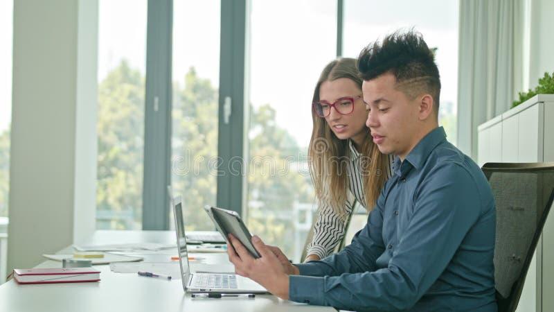 Zwei Leute, die Ideen unter Verwendung Digital-Tablets besprechen stockfotografie