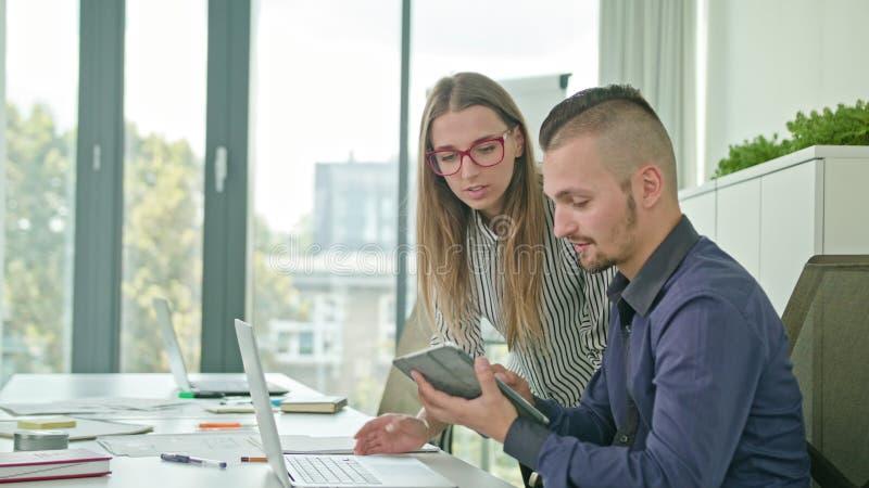 Zwei Leute, die Ideen unter Verwendung Digital-Tablets besprechen lizenzfreie stockfotografie