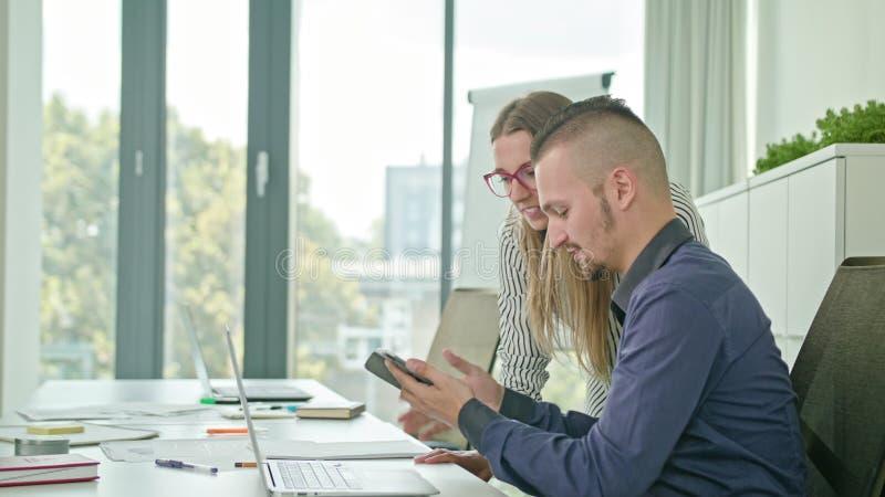 Zwei Leute, die Ideen unter Verwendung Digital-Tablets besprechen stockbild