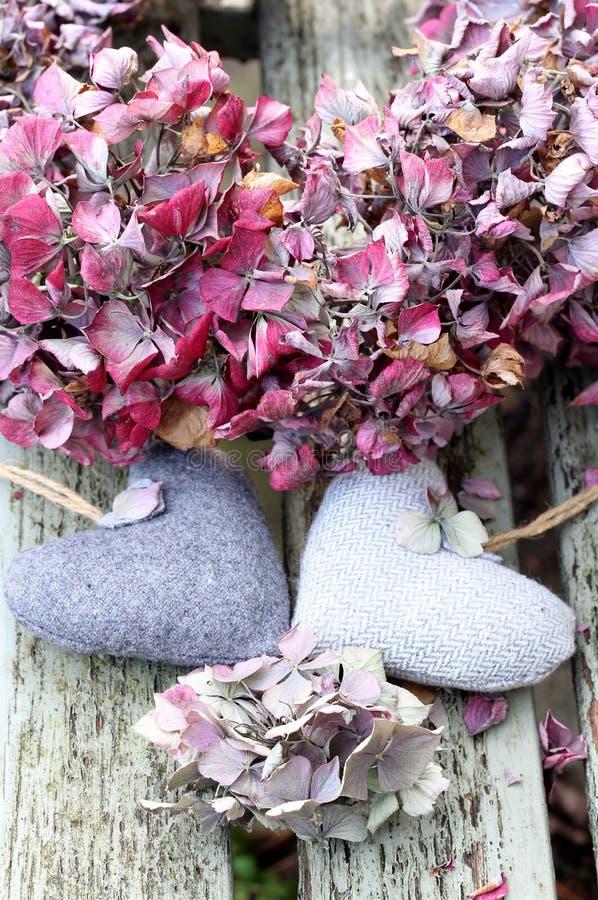 Zwei Liebesherzen mit getrocknetem blassem - rosa hyrdragea Kranz lizenzfreie stockbilder
