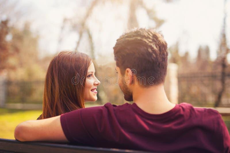 Zwei Liebhaber, die auf einer Bank in einem Park sitzen stockbild
