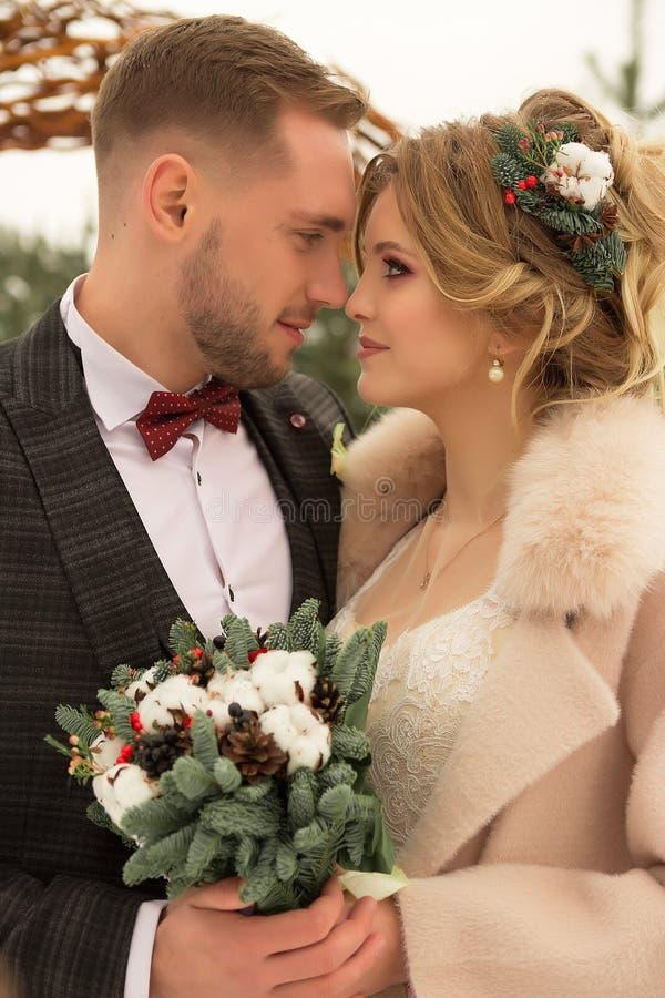 Zwei Liebhaber, ein Mann und eine Frau, eine Hochzeit im Winter Braut- und Bräutigamliebe gegen den Hintergrund des Dekors und de stockbilder