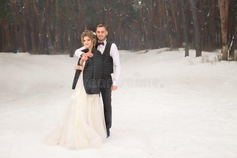 Zwei Liebhaber im Wald, ein glückliches Paar, Umarmen, sehnend Lächeln, Braut und Bräutigam Heirat im Winter Anzug und Hochzeitsk stockfotografie