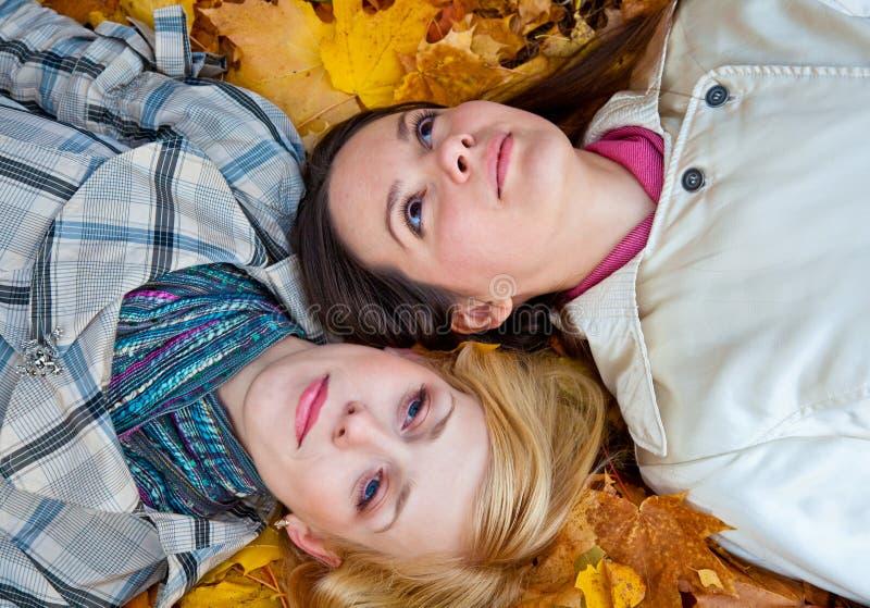 Zwei liegenmädchen in den Blättern lizenzfreies stockfoto