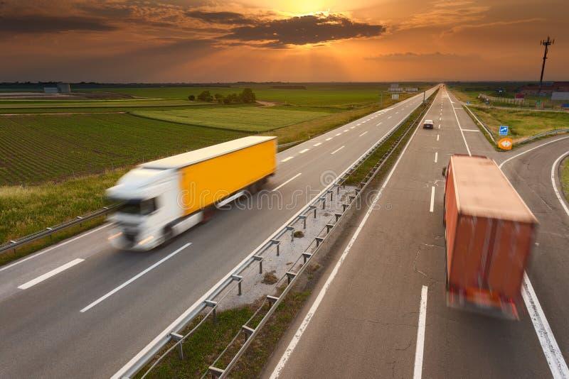 Zwei LKWs in der Bewegungsunschärfe auf der Autobahn bei Sonnenuntergang lizenzfreie stockfotos