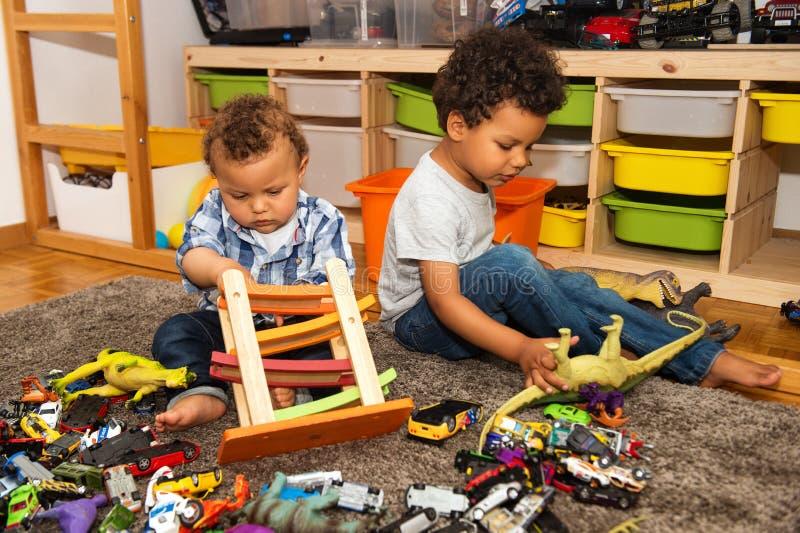 Zwei lustig und unordentliche Babybrüder, die zusammen spielen stockfotografie