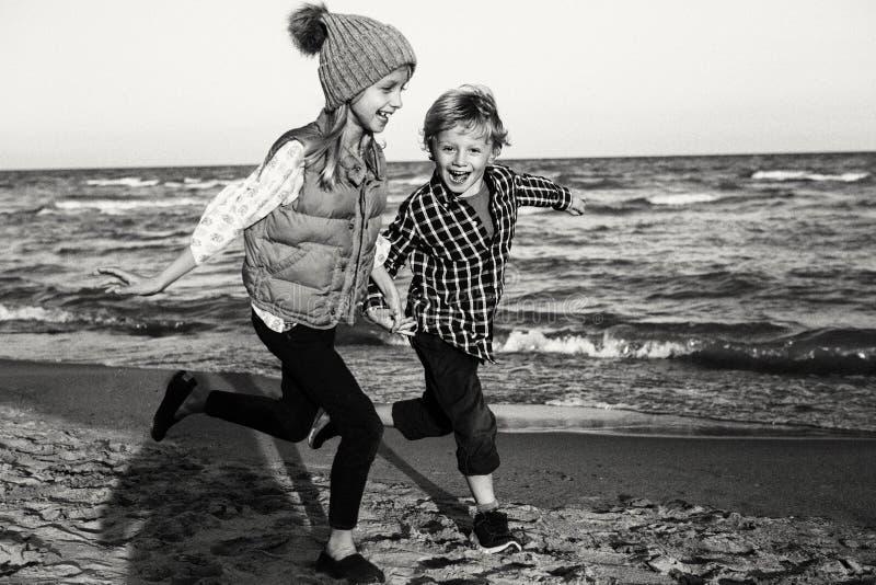 Zwei lustige kaukasische Kinder scherzt die Freunde, die das Laufen auf Ozeanseestrand spielen lizenzfreies stockbild