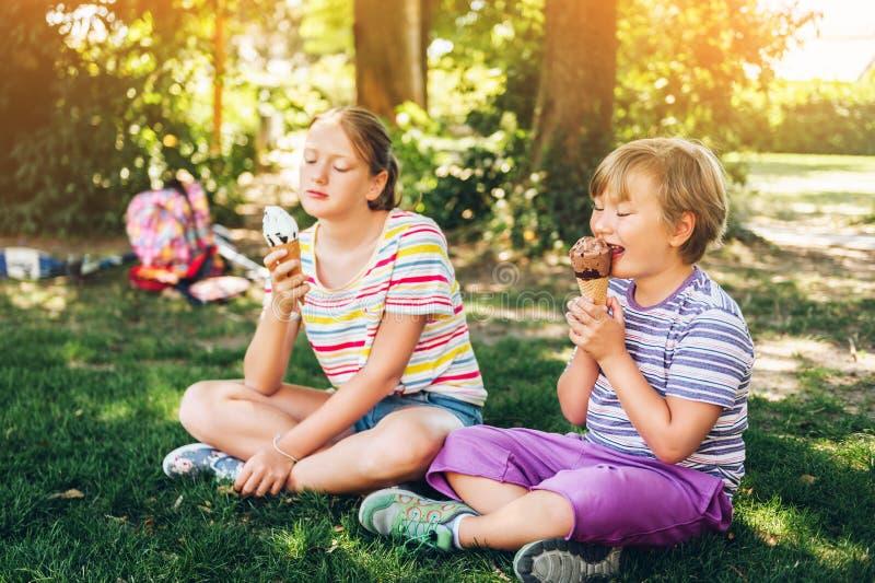 Zwei lustige Kinder, die Eiscreme im Sommerpark essen stockbilder