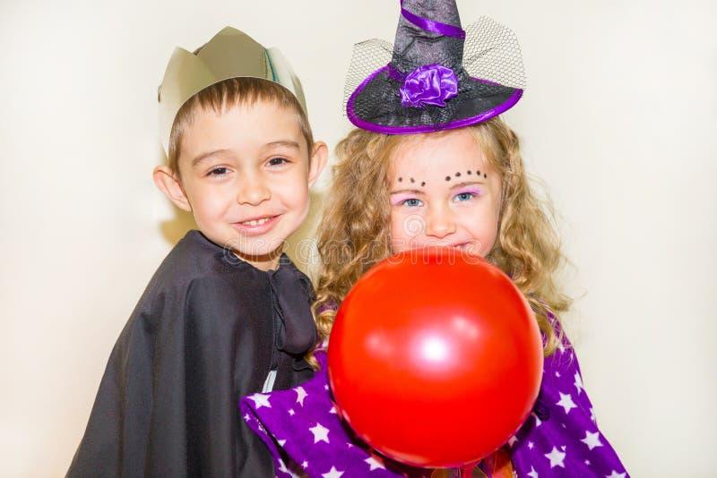 Zwei lustige Kinder, die Hexen- und Vampirskostüm auf Halloween tragen stockfotografie