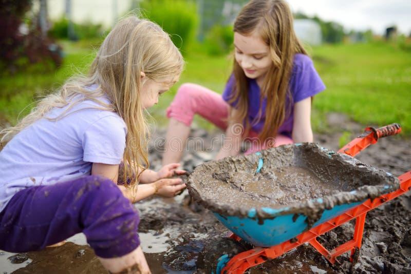 Zwei lustige kleine Mädchen, die in einer großen nassen Schlammpfütze am sonnigen Sommertag spielen Kinder, die beim Graben in sc stockbild