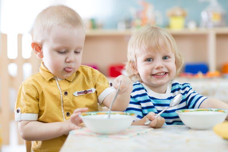 Zwei lustige lächelnde Kleinkinder, die im Kindergarten essen lizenzfreie stockfotos