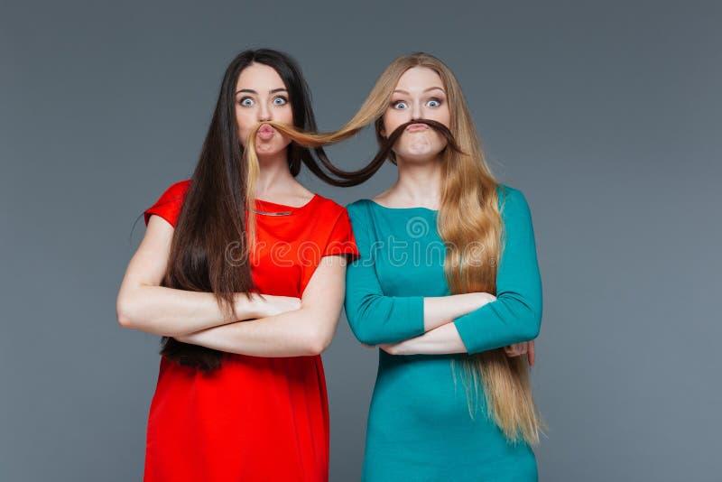Zwei lustige Mädchen, die Schnurrbart mit ihrem Haar herstellen lizenzfreies stockfoto