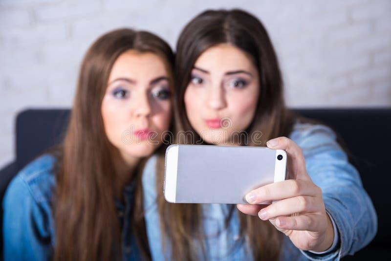 Zwei lustige Mädchen, die selfie Foto mit intelligentem Telefon machen lizenzfreies stockbild