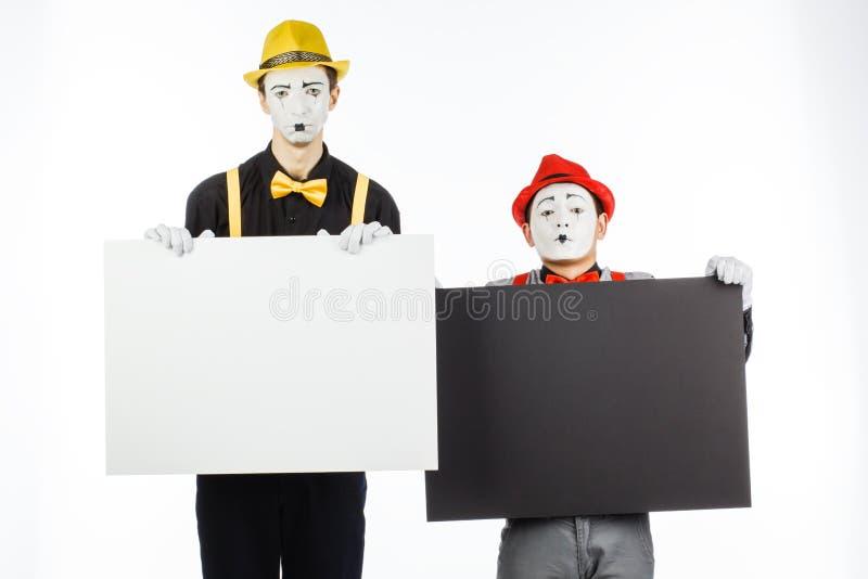 Zwei lustige Pantomimen, die einen weißen freien Raum auf einem weißen Hintergrund halten lizenzfreie stockbilder