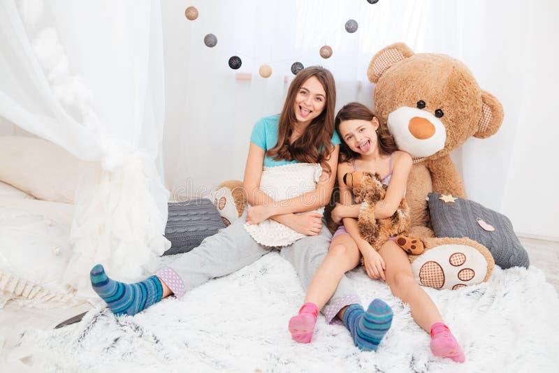 Zwei lustige reizende sitzende und darstellende Schwestern leckt i auf lizenzfreie stockfotos