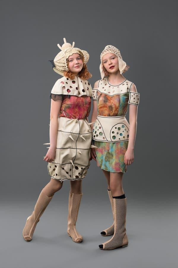 Zwei Mädchen in den bunten Kleidern und im Hutporträt stockfotos