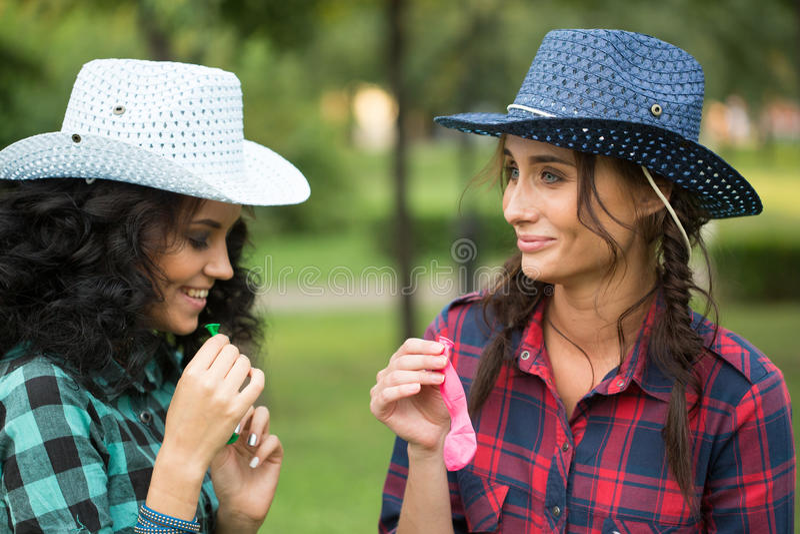 Zwei Mädchen in den Cowboyhüten mit Ballonen stockfotos