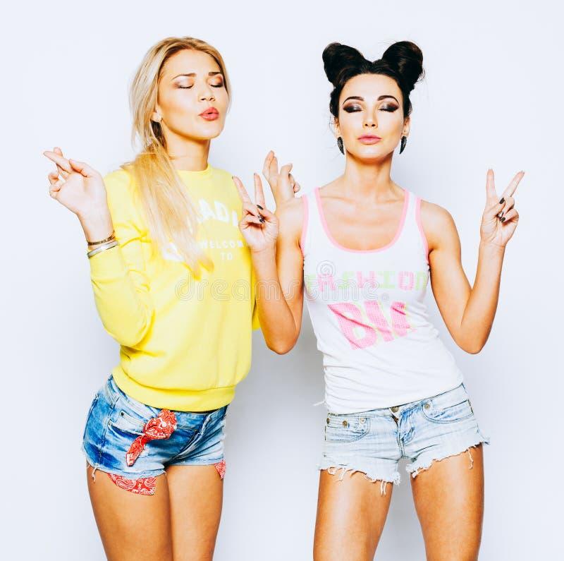Zwei Mädchen in den hellen Modeausstattungen, kurze Hosen Meditieren Sie entspannt mit den geschlossenen Augen, die ein Zeichen d stockfotografie