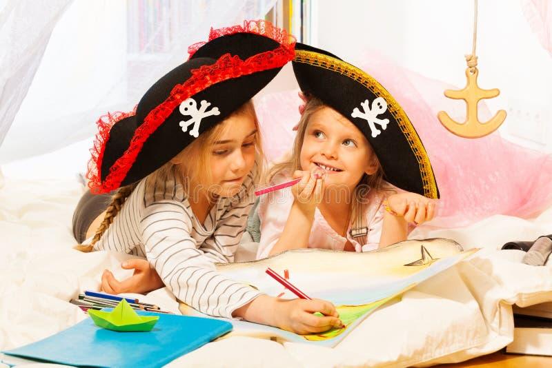 Zwei Mädchen in den tricorns, welche die Schatzkarte zeichnen stockbild