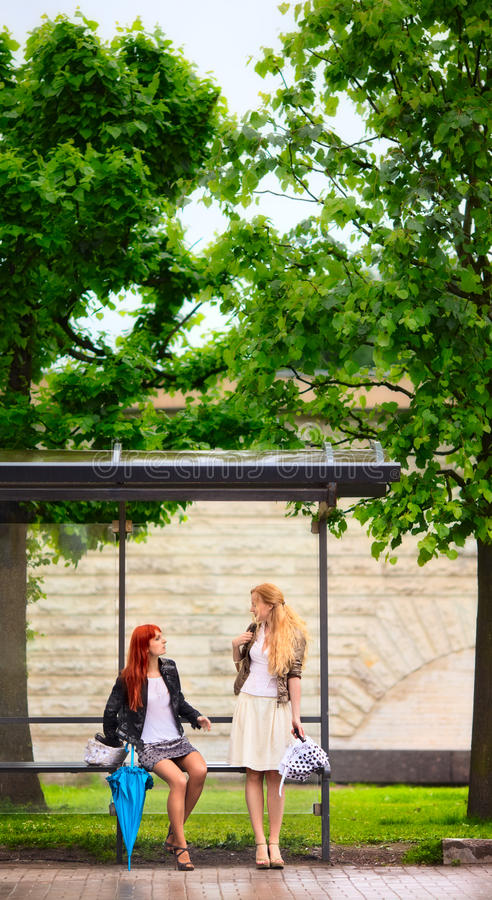 Zwei Mädchen An Der Bushaltestelle Lizenzfreie Stockfotografie