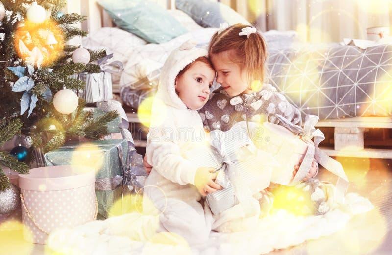Zwei Mädchen der kleinen Schwester öffnen ihre Geschenke am Weihnachtsbaum morgens auf der Plattform lizenzfreie stockbilder