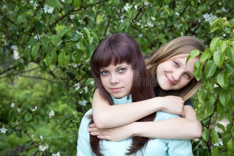 Zwei Mädchen des Jugendlichen gegen Birne lizenzfreie stockfotografie
