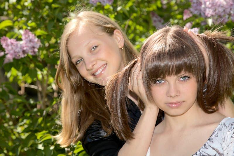 Zwei Mädchen des Jugendlichen gegen eine Flieder stockfotos