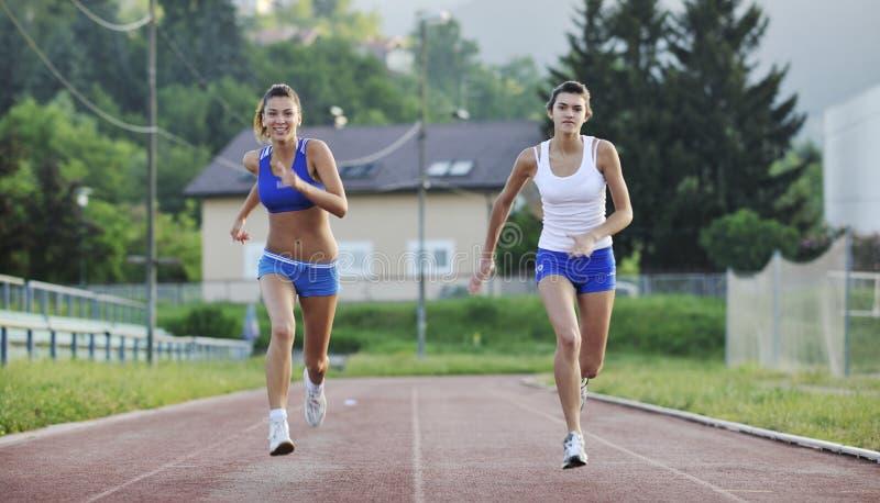 Zwei Mädchen, die auf athletische Rennenspur laufen lizenzfreie stockfotografie