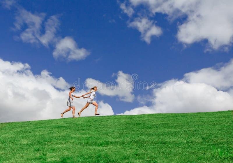 Zwei Mädchen, die auf das Feld laufen lizenzfreie stockfotos