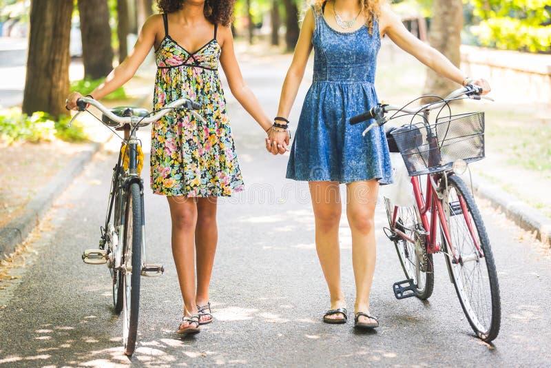 Zwei Mädchen, die auf das Straßenhändchenhalten gehen stockfoto
