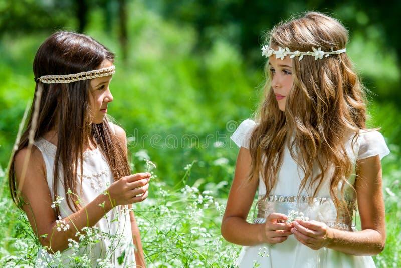 Zwei Mädchen, die auf dem Blumengebiet stehen. stockbild