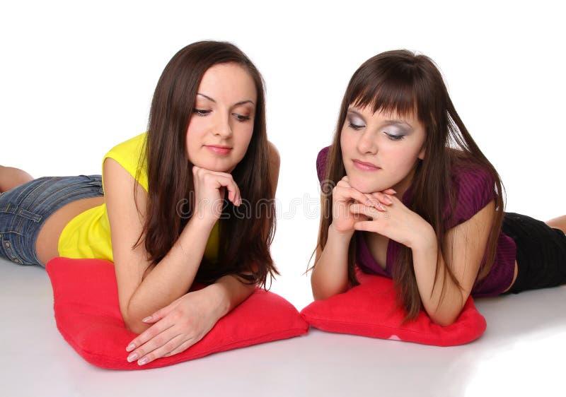 Zwei Mädchen, die auf dem Fußboden liegen stockfoto