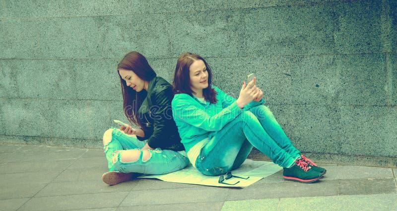 Zwei Mädchen, die auf der Straße sitzen stockbild