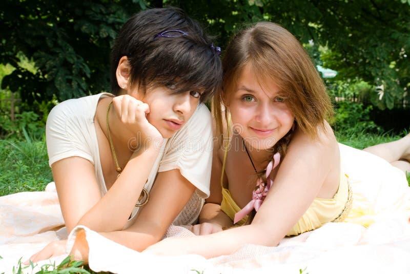 Zwei Mädchen, die auf die Bettdecke nach grünem Gras legen lizenzfreies stockfoto