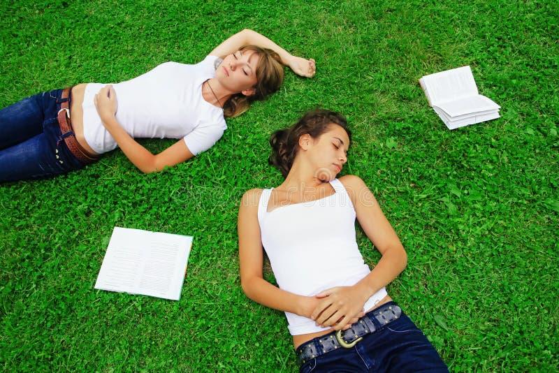 Zwei Mädchen, die auf Gras liegen lizenzfreie stockfotografie