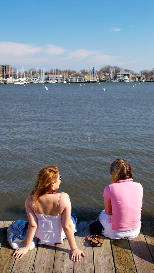 Zwei Mädchen, die auf Promenade sitzen stockbilder