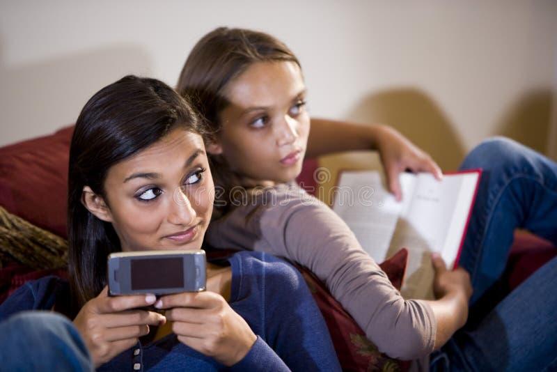 Zwei Mädchen, die auf Sofa stützen, schauen oben vom Texting stockfoto