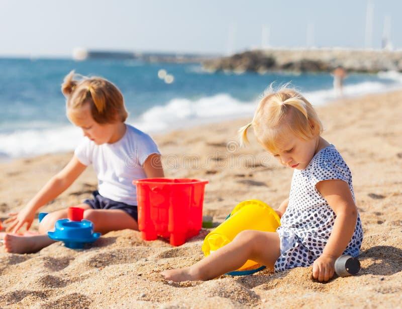 Zwei Mädchen, die auf Strand spielen stockfotos