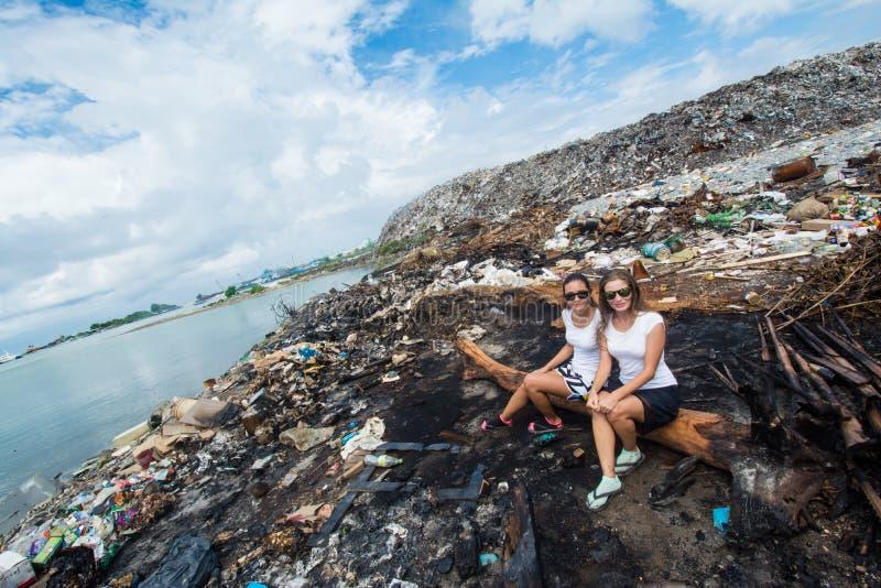 Zwei Mädchen, die auf totem Baum an der Müllkippe sitzen lizenzfreies stockfoto