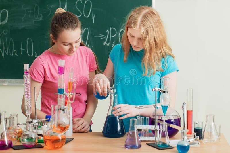 Zwei Mädchen, die chemische Experimente tun lizenzfreie stockbilder
