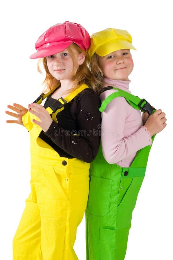 Zwei Mädchen, die colorfull Dungarees tragen lizenzfreie stockfotografie