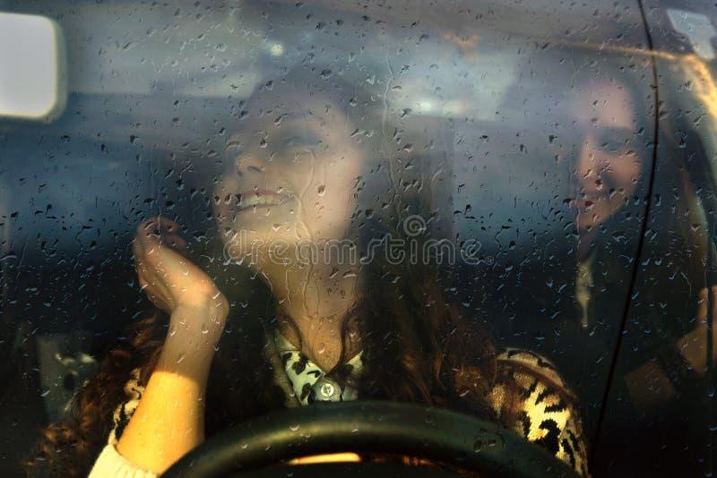 Zwei Mädchen, die in das Auto im Regen reiten stockbild