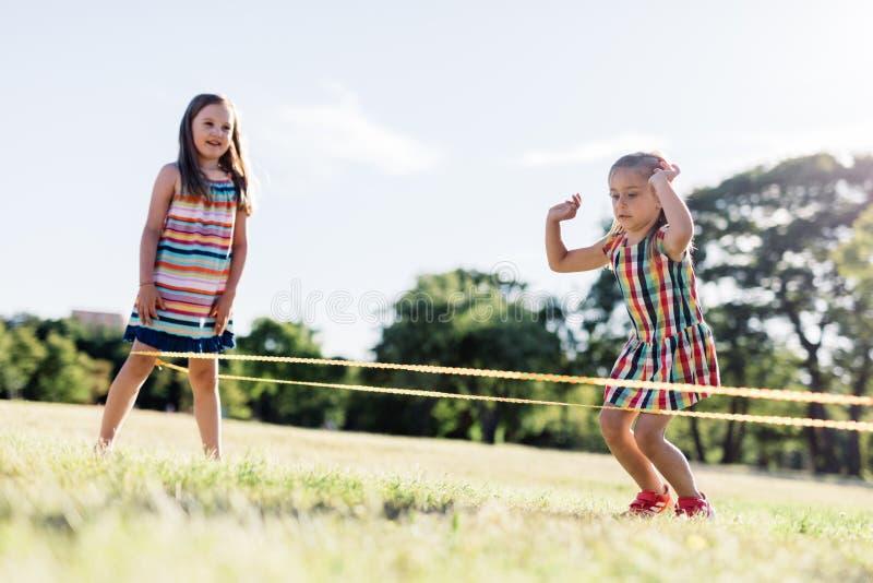 Zwei Mädchen, die das chinesisches Springen spielen, fangen den Park ein lizenzfreies stockbild