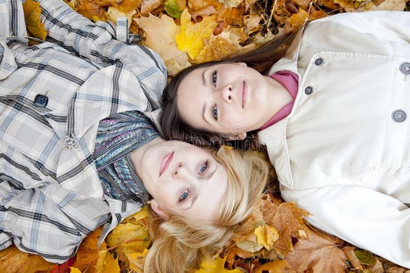 Zwei Mädchen, die in den Blättern liegen stockfotografie