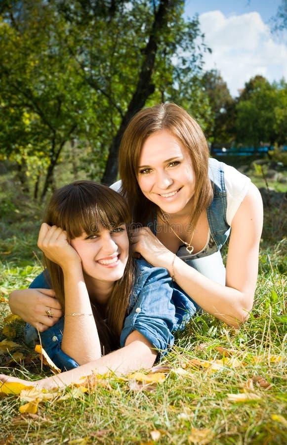 Zwei Mädchen, die in den Herbstblättern liegen lizenzfreie stockfotografie