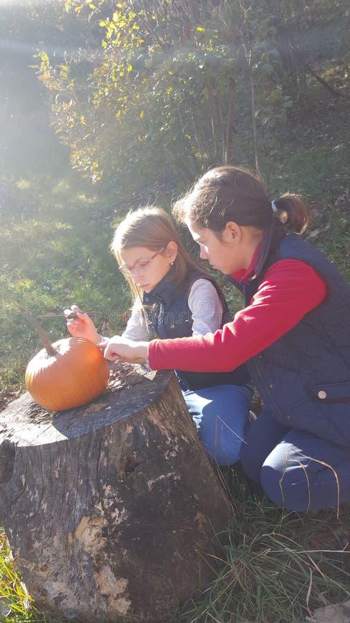 Zwei Mädchen, die einen Kürbis schnitzen stockfoto