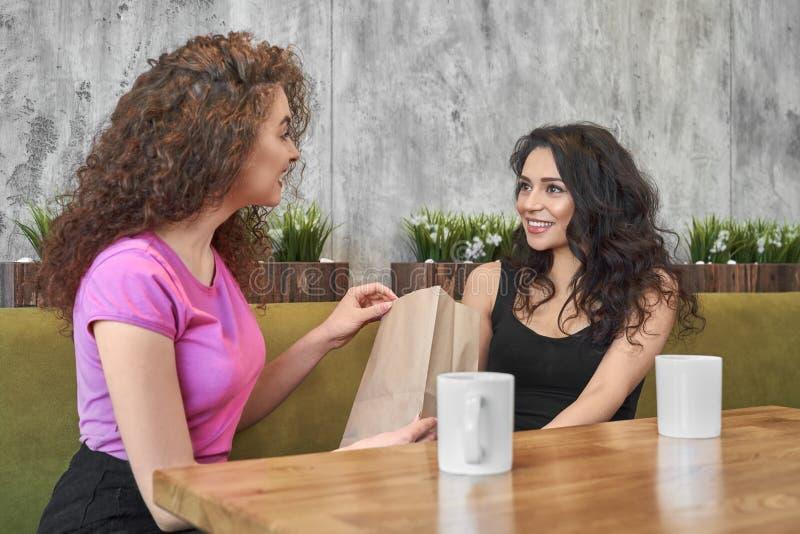 Zwei Mädchen, die im Café, Geschenk gebend sitzen lizenzfreies stockbild