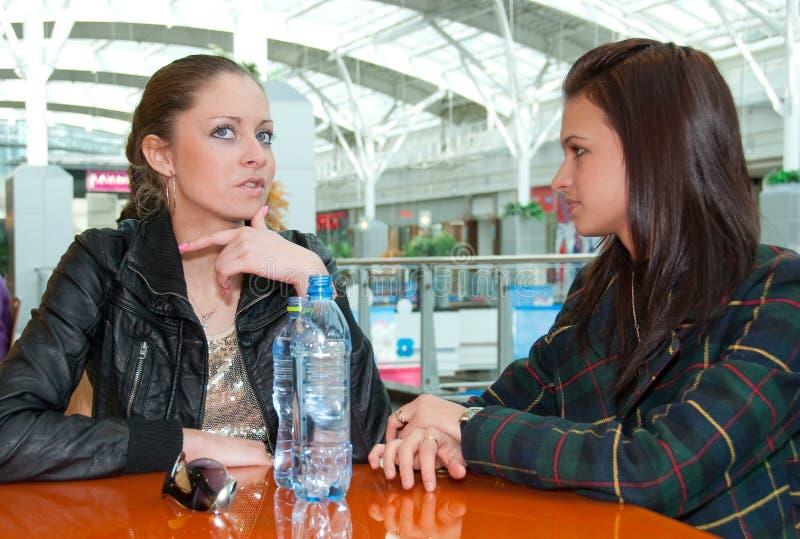 Zwei Mädchen, die im Nahrungsmittelgericht in einem Mall sprechen stockfotos